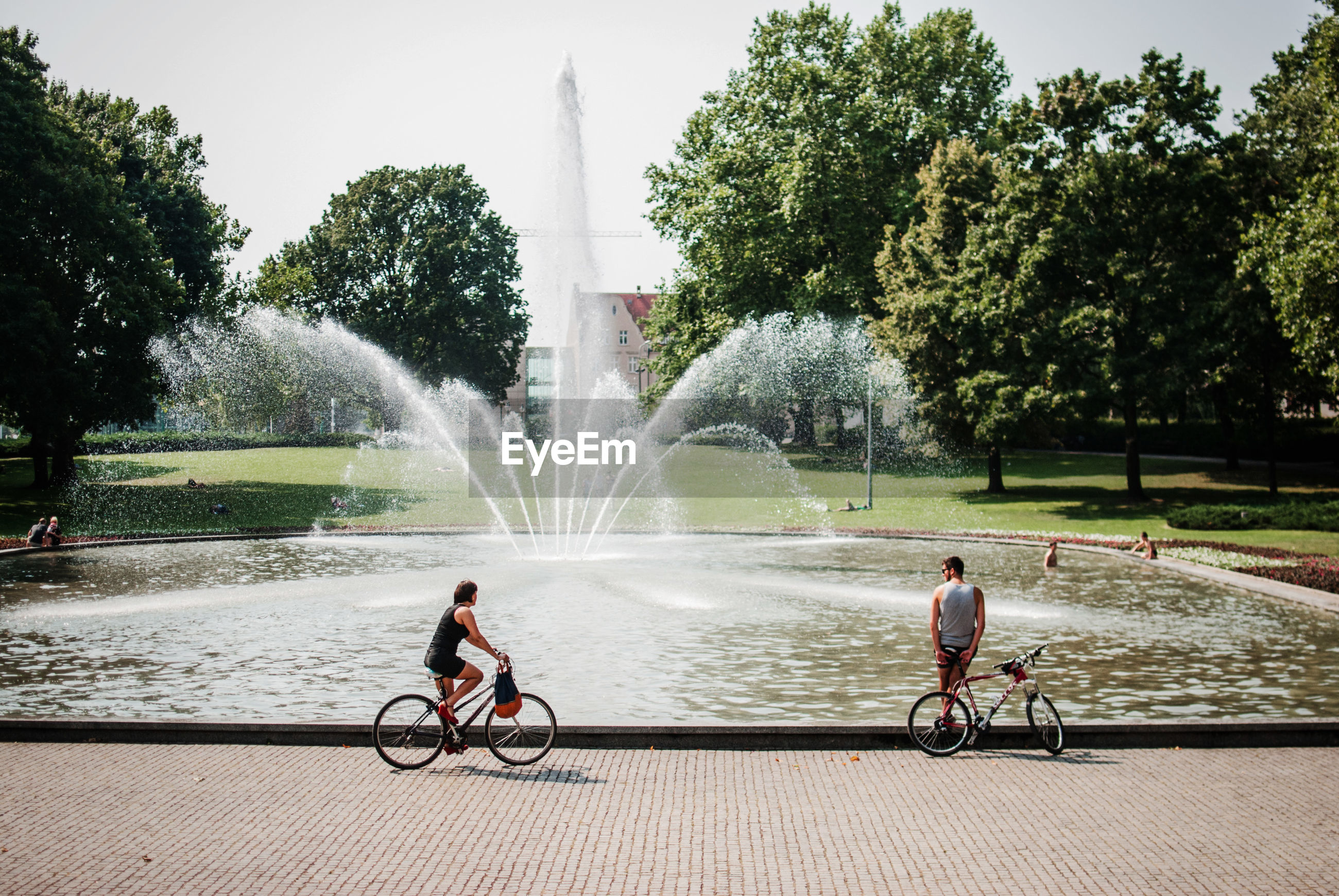 Man and woman with bicycles on footpath against fountain at park