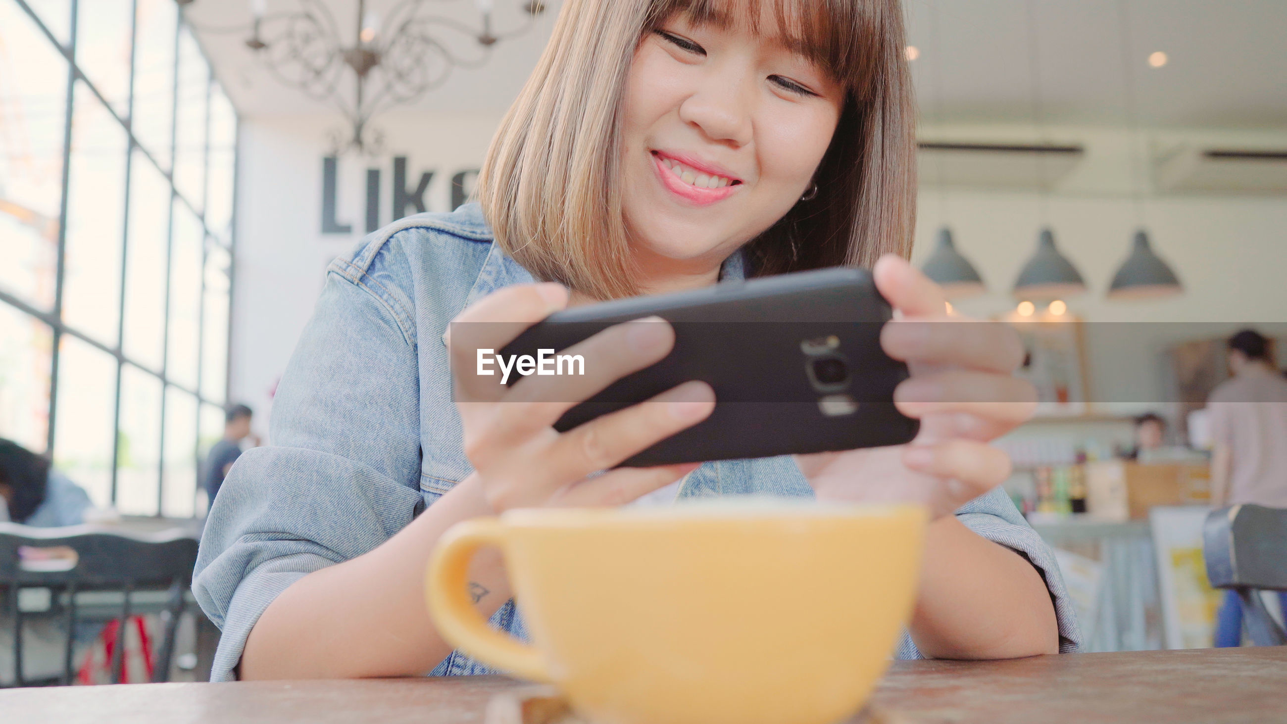 Smiling young woman photographing cup on table in cafe