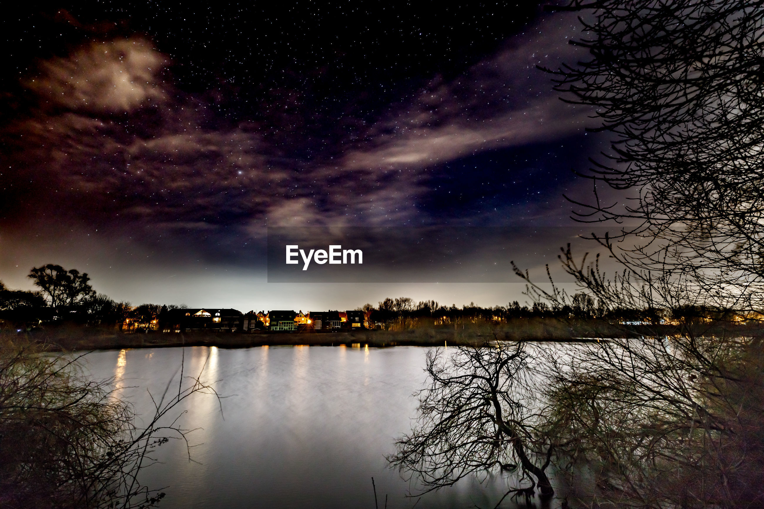 REFLECTION OF TREES ON LAKE AGAINST SKY AT NIGHT