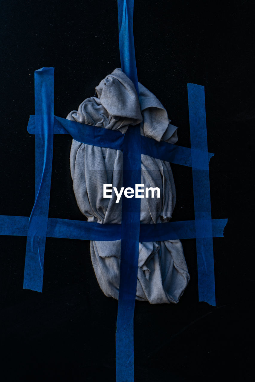 no people, blue, close-up, human representation, art and craft, representation, creativity, black background, indoors, sculpture, metal, architecture, night, male likeness, religion, statue, spirituality, belief, cross