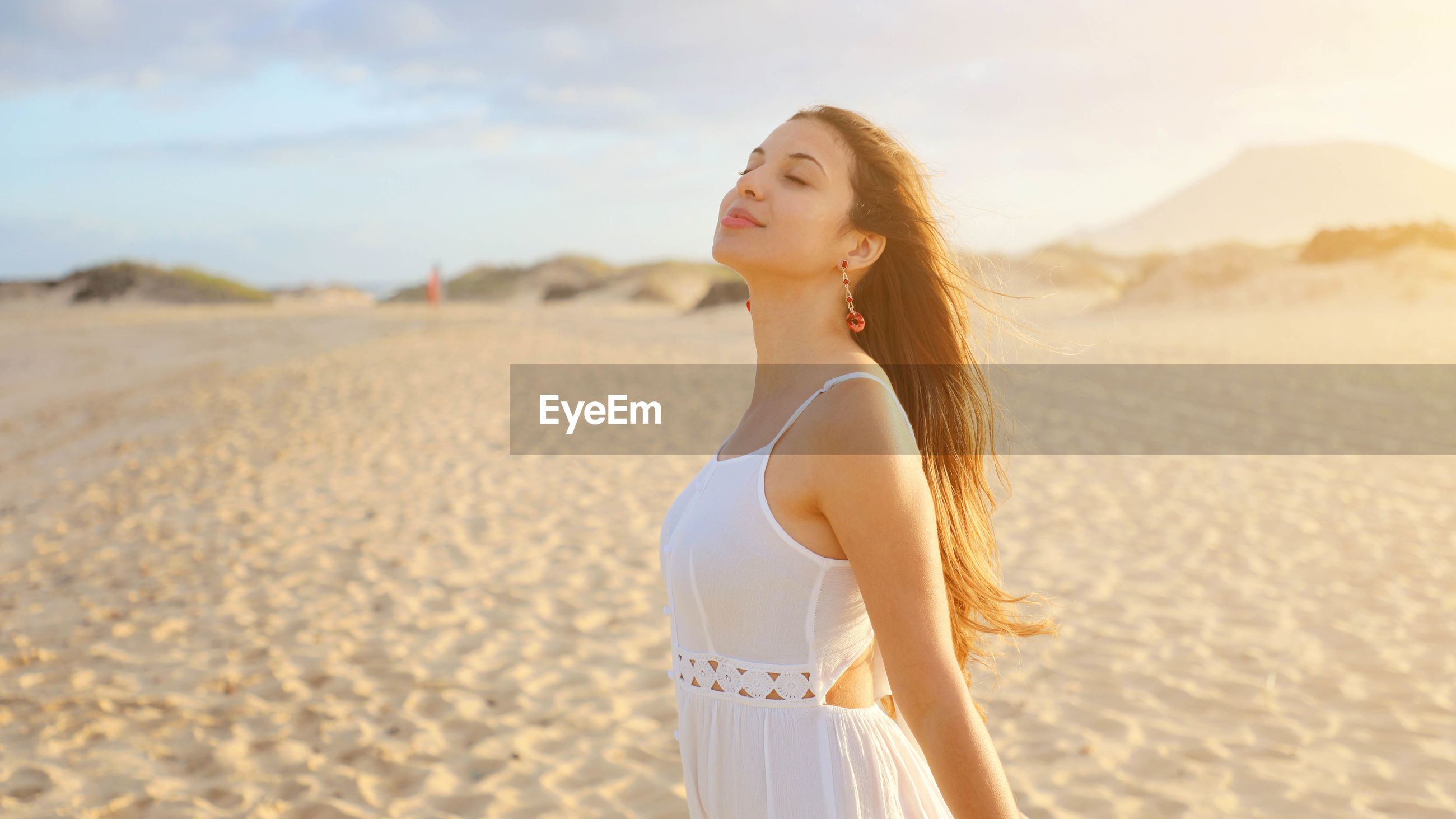 Smiling young woman with eyes closed standing on sand at desert