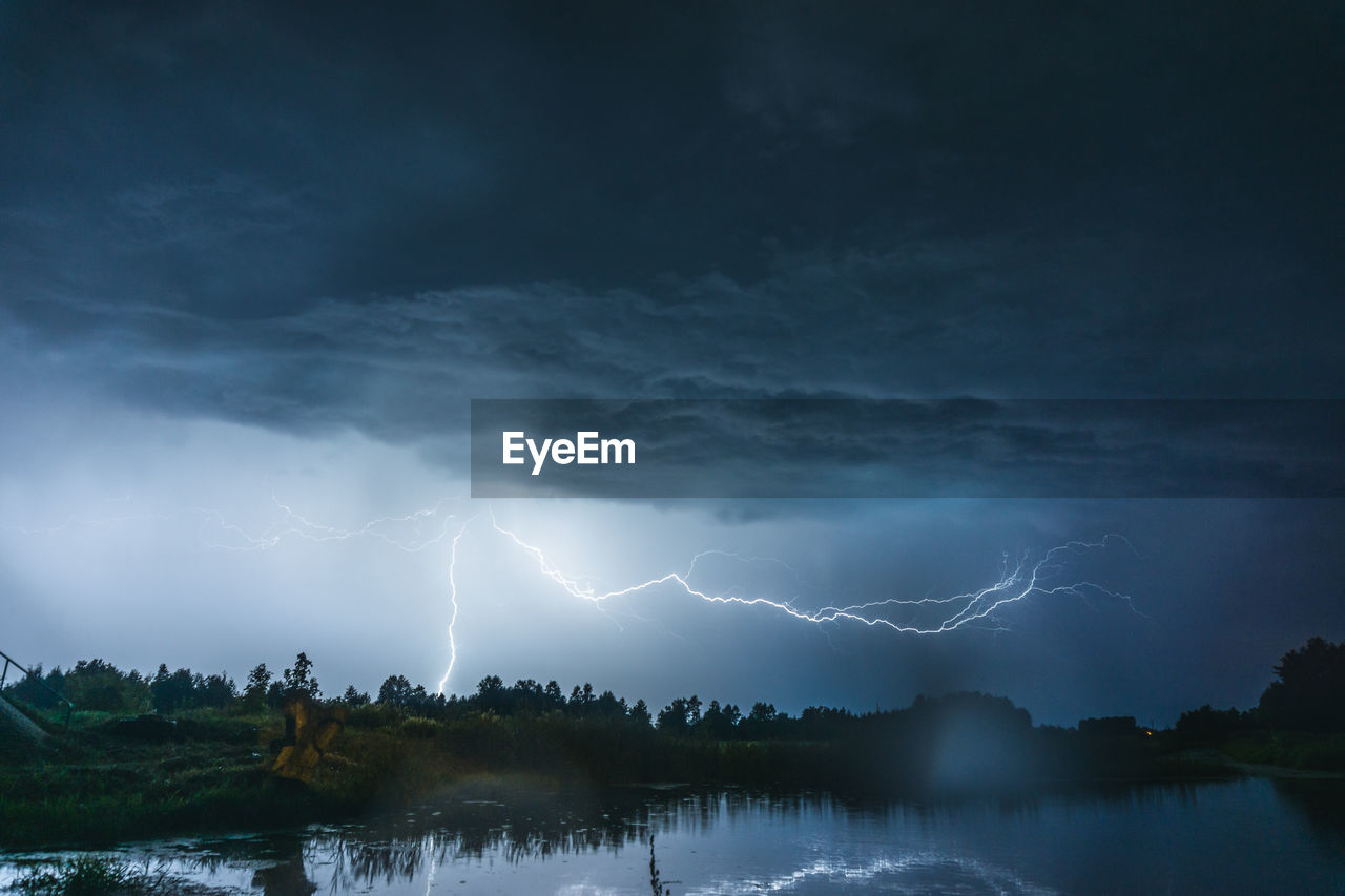 Scenic View Of Lightning Over Lake At Dusk