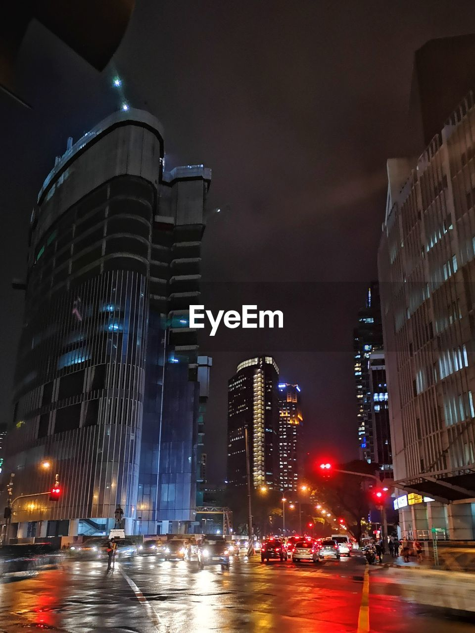 illuminated, building exterior, architecture, night, city, built structure, office building exterior, building, transportation, tall - high, modern, skyscraper, street, car, land vehicle, office, motor vehicle, mode of transportation, sky, road, no people, cityscape, outdoors, nightlife, financial district