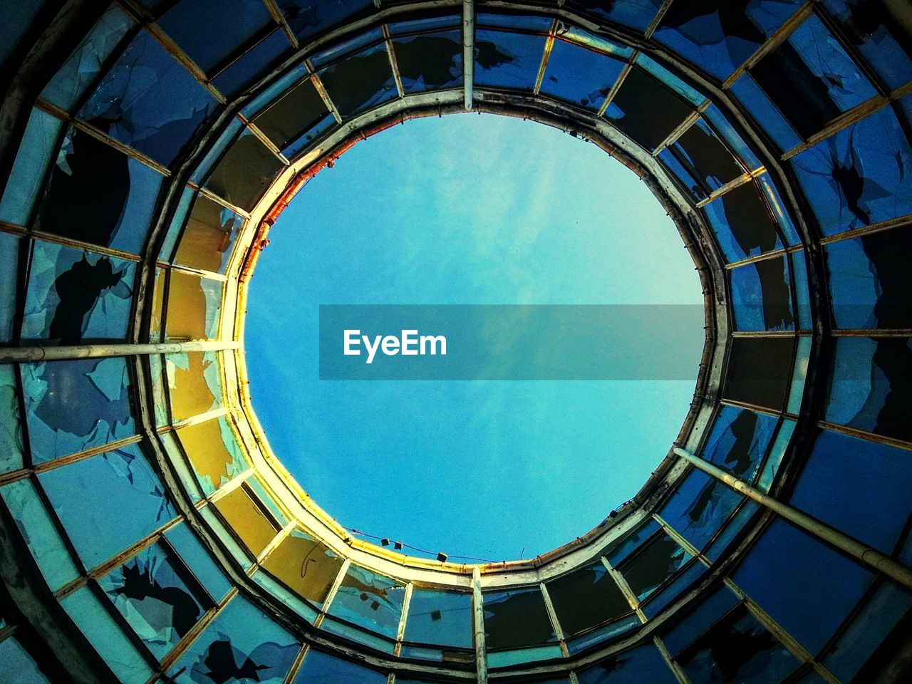 Directly Below Shot Of Blue Sky Seen Through Circular Ceiling