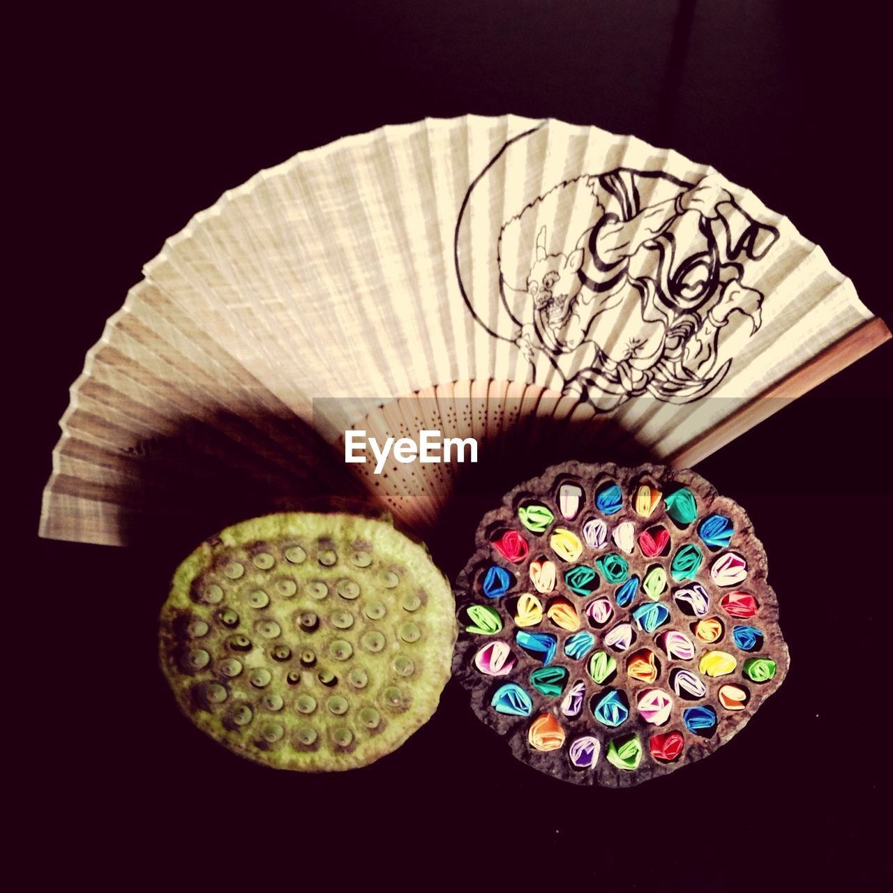 Directly Below Shot Of Artificial Flowers And Folding Fan Against Black Background