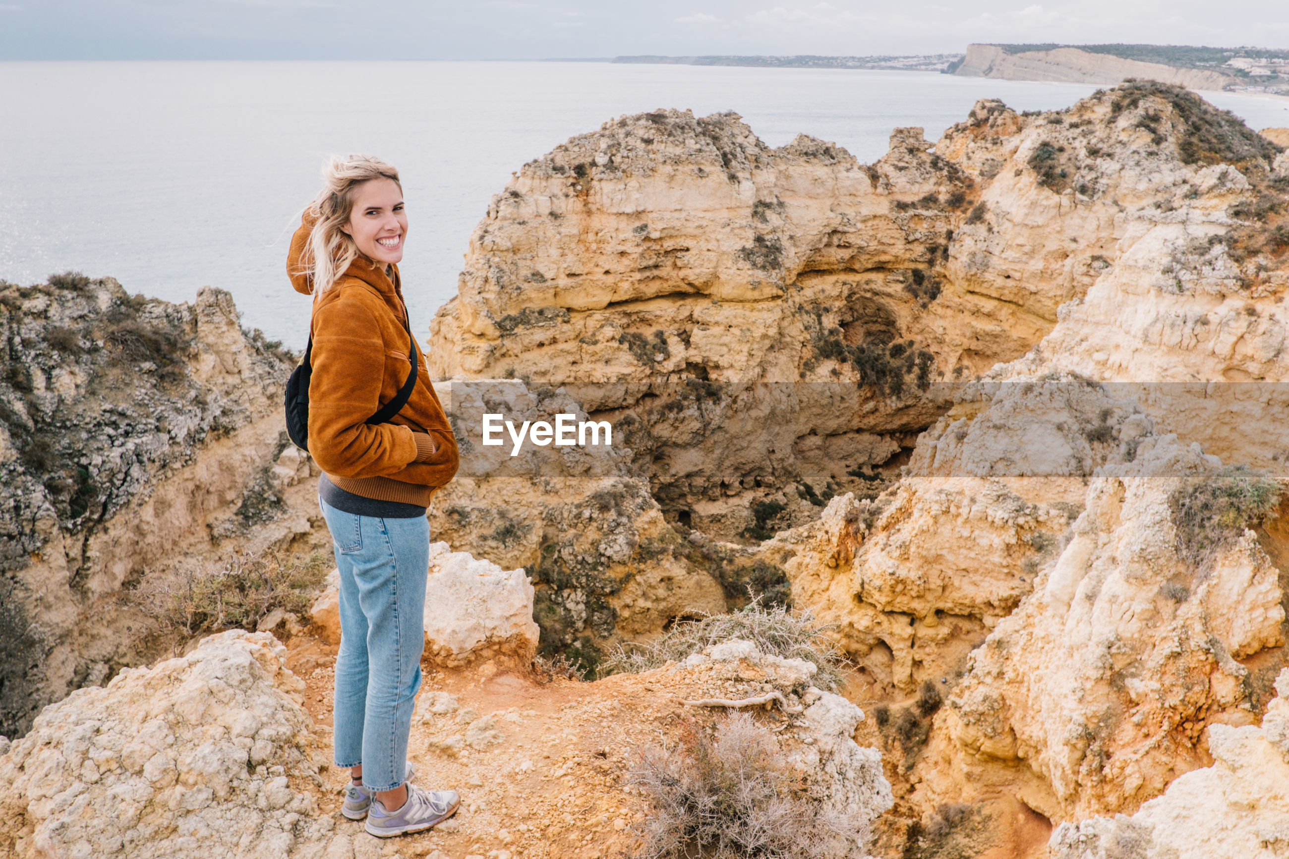 Portrait of smiling young woman standing on cliff