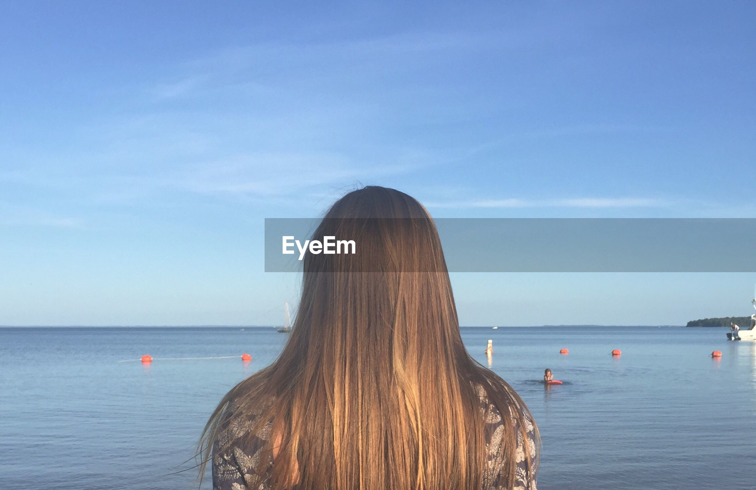 Rear view of woman at beach against blue sky