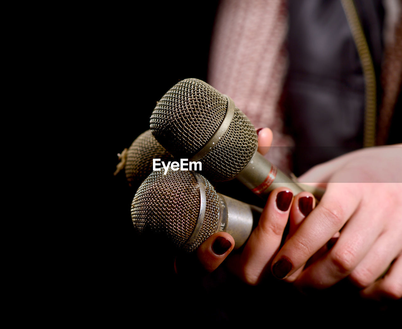 Cropped Hands Of Woman Holding Microphones Against Black Background