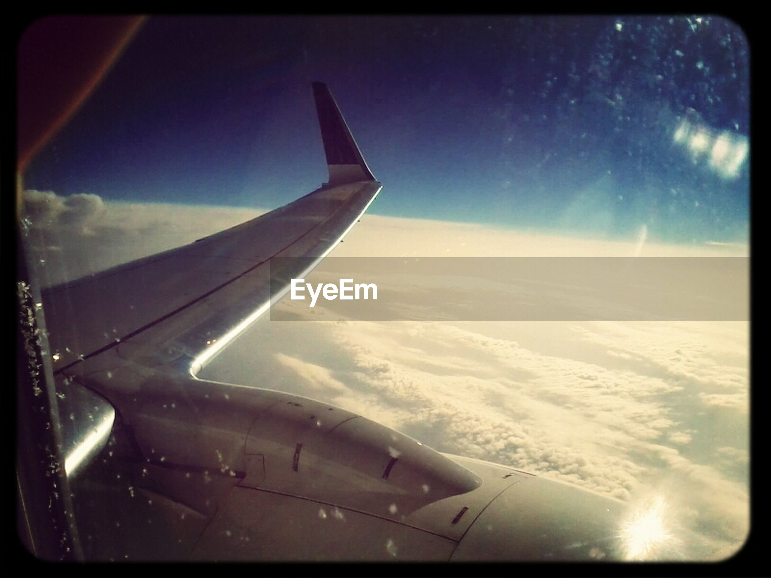 transfer print, airplane, air vehicle, aircraft wing, transportation, auto post production filter, flying, mode of transport, sky, travel, part of, landscape, journey, aerial view, cloud - sky, mid-air, nature, on the move, sunlight, scenics