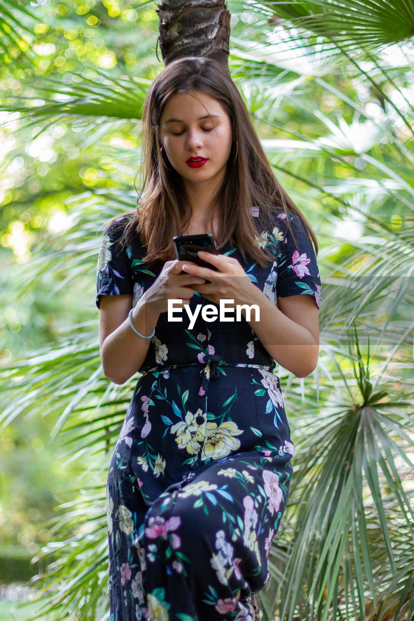 Young woman using mobile phone while standing against trees
