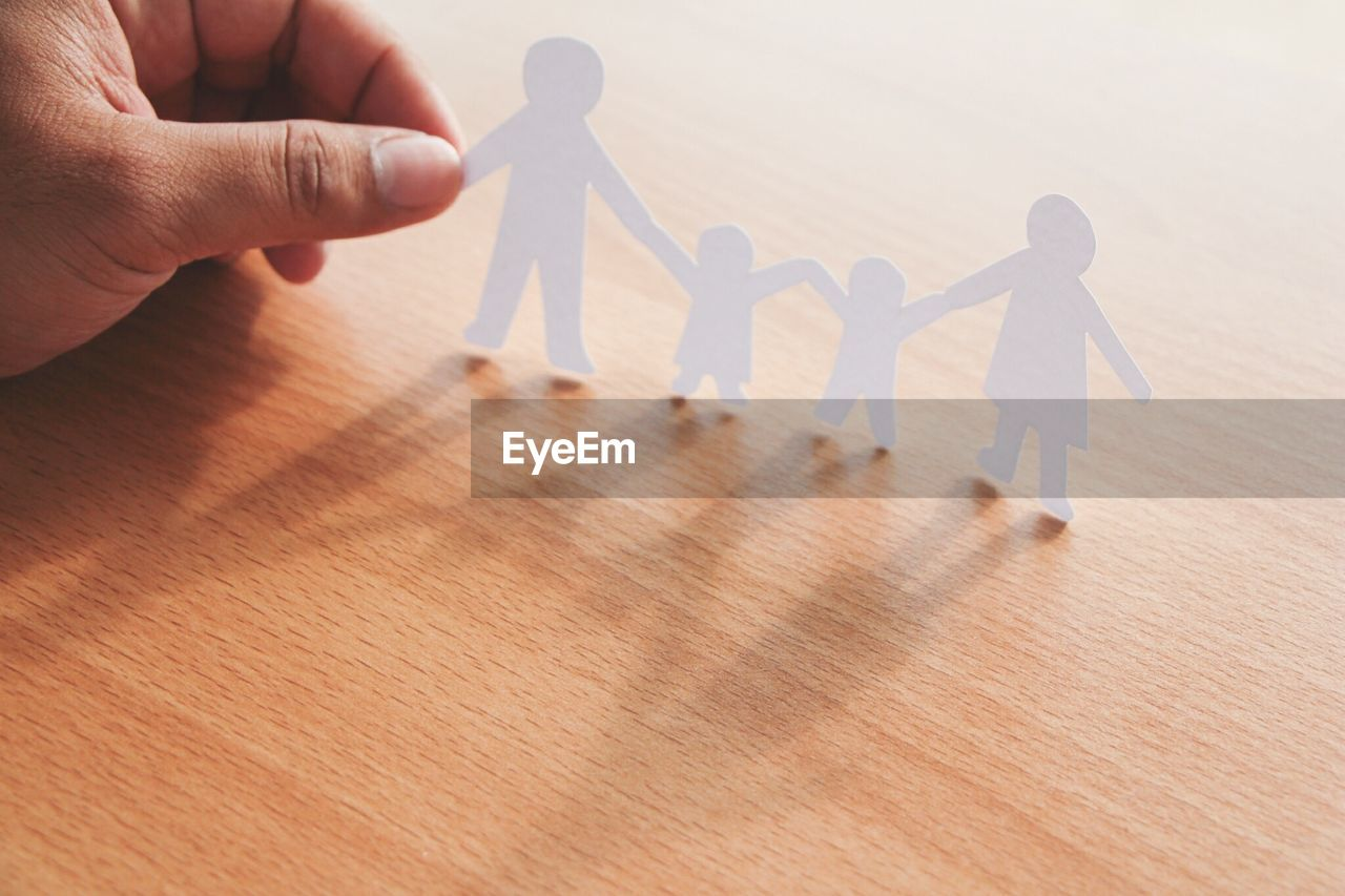 Cropped hand holding family human representations on wooden table