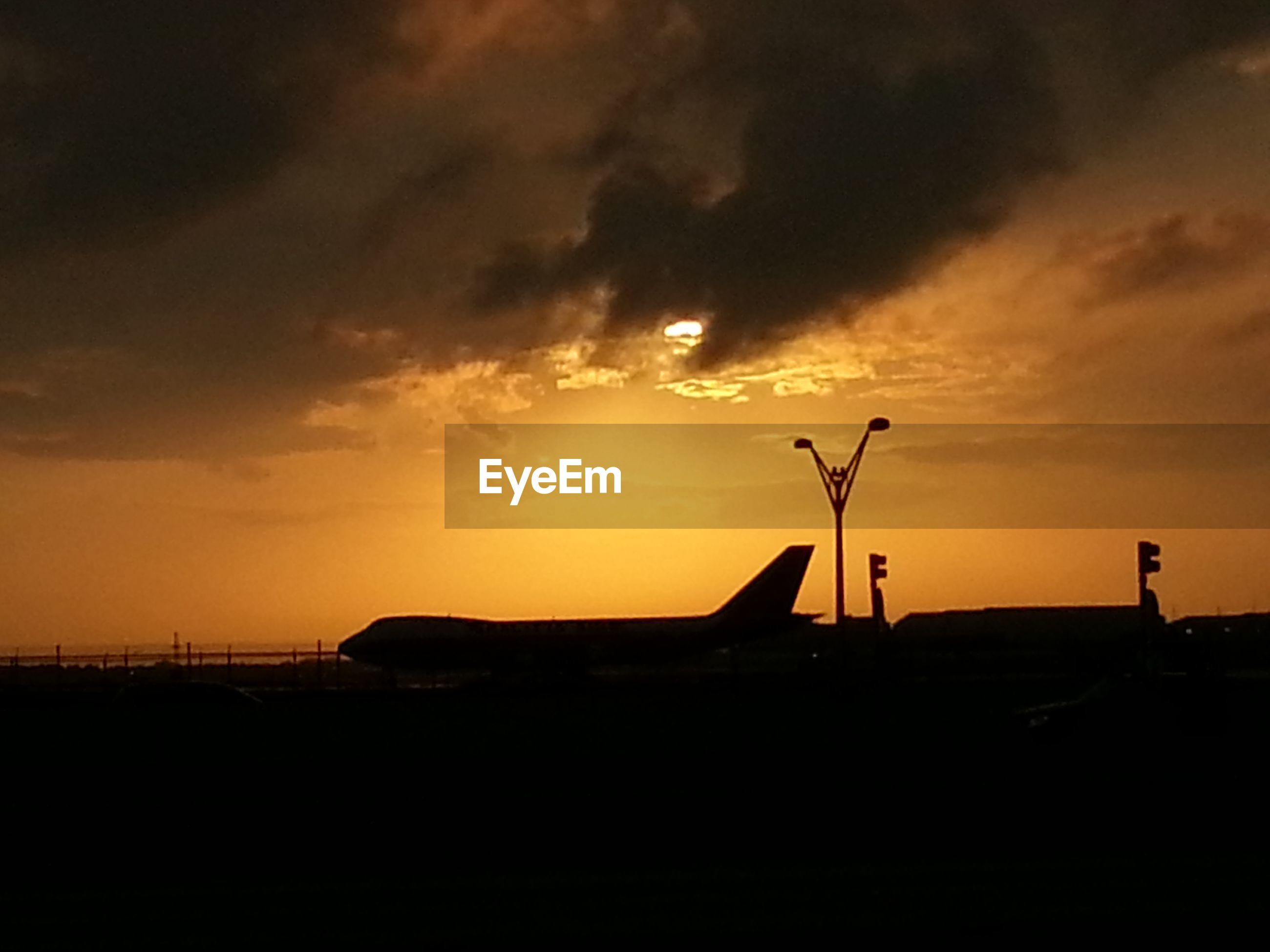 Silhouette airplane on airport runway against orange sky