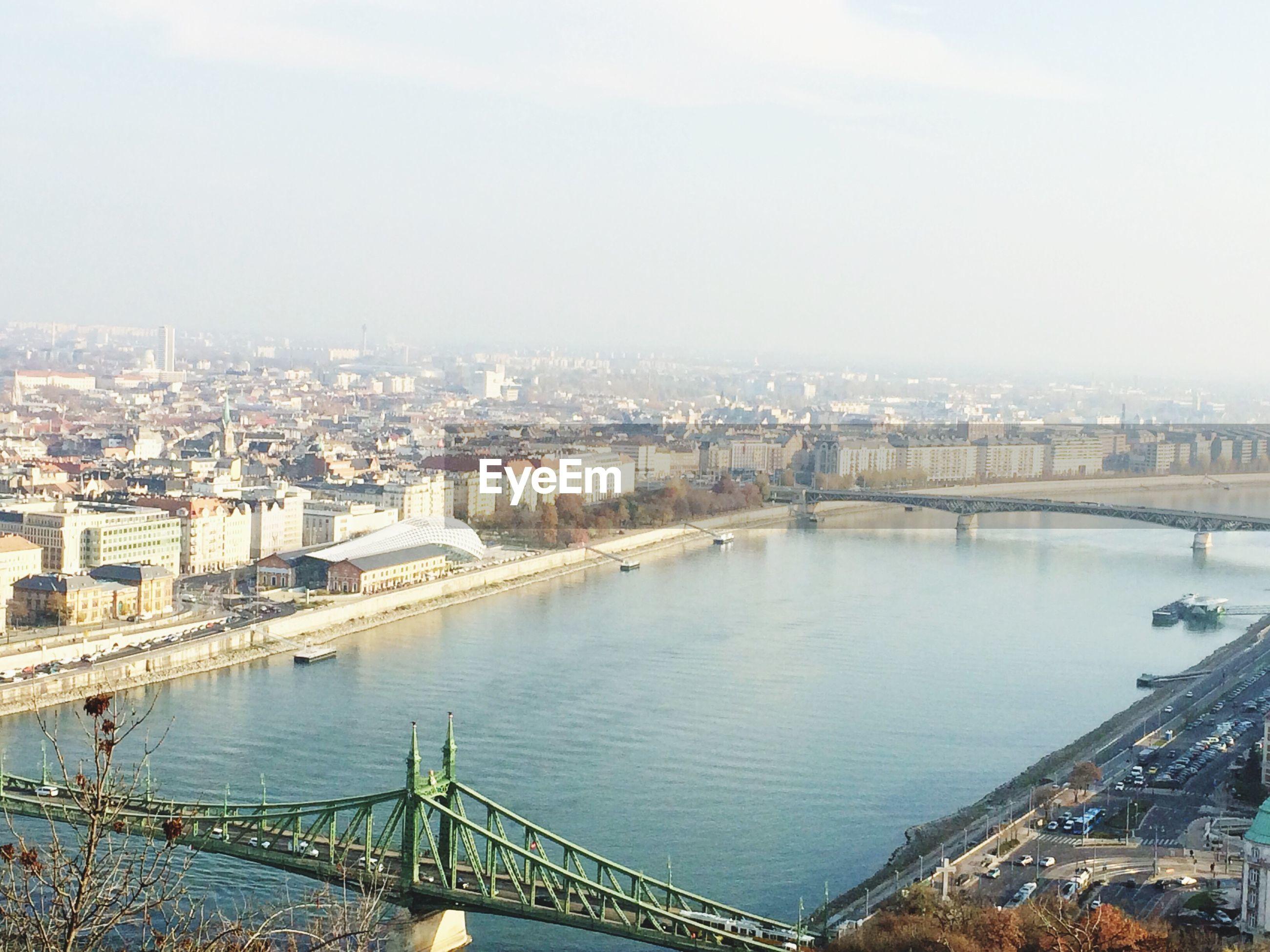 Bridges over river in city against sky