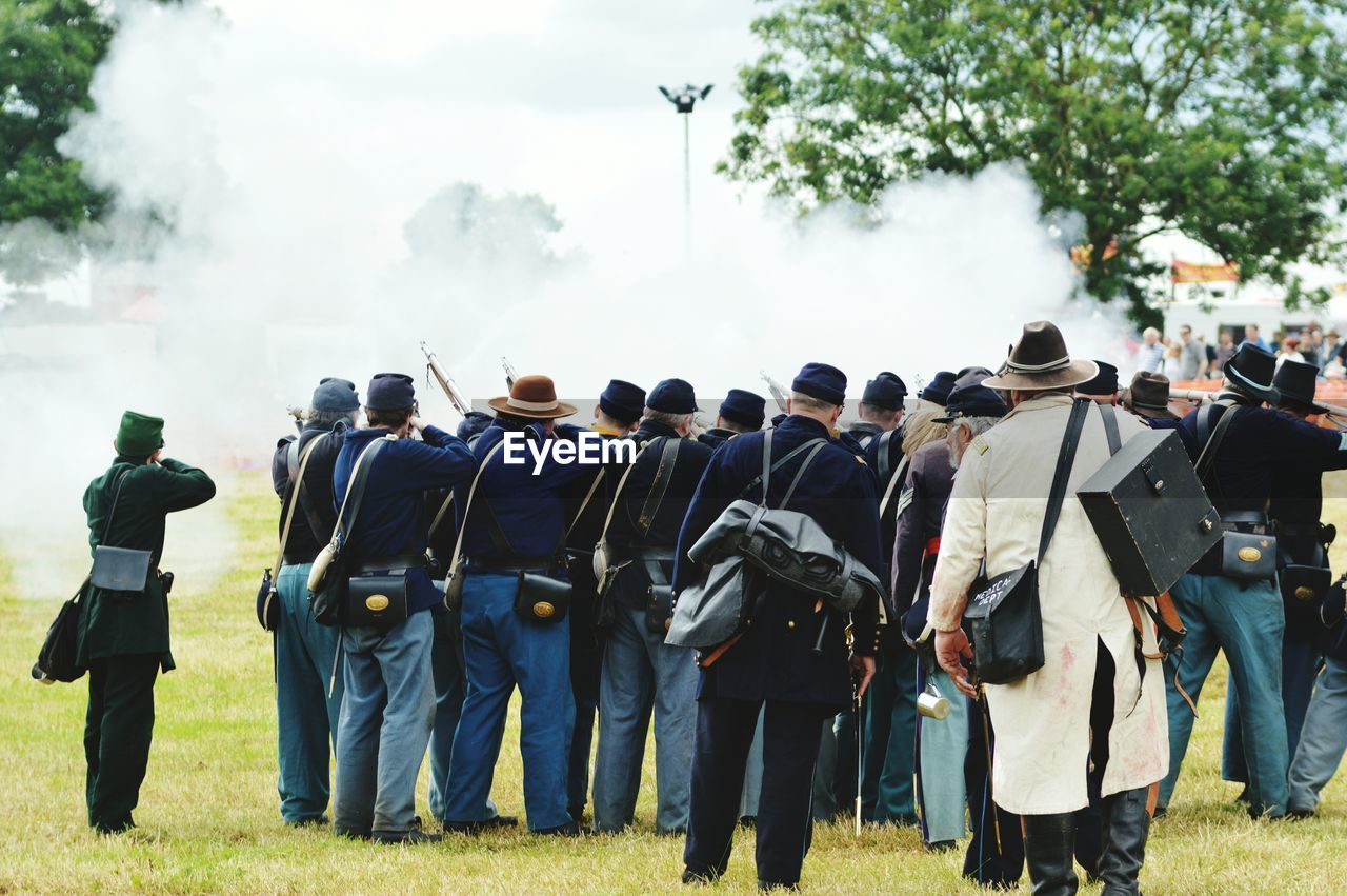 Rear view of army soldiers shooting on field