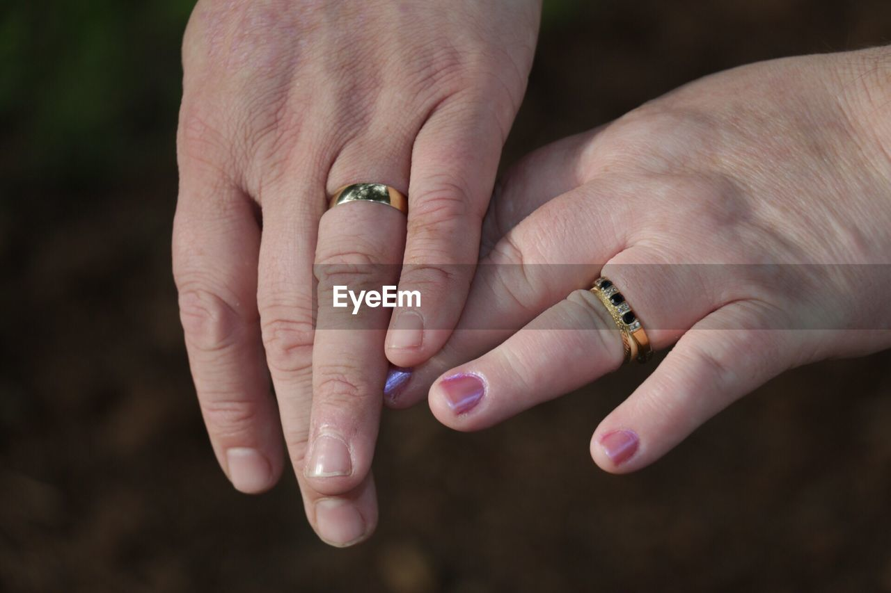 Cropped hands of couple wearing gold rings