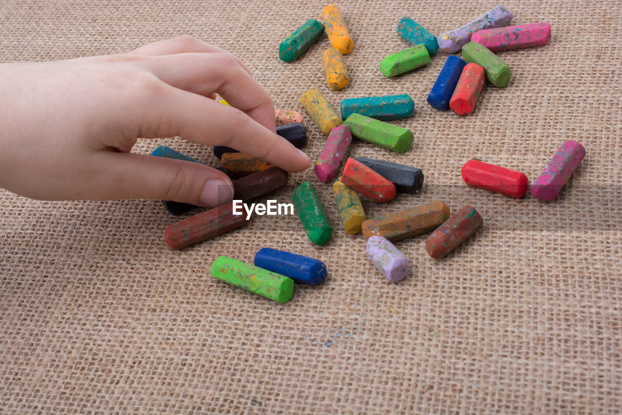 human hand, hand, human body part, one person, real people, body part, finger, multi colored, human finger, indoors, unrecognizable person, holding, art and craft, close-up, lifestyles, leisure activity, high angle view, creativity, personal perspective, nail, human limb