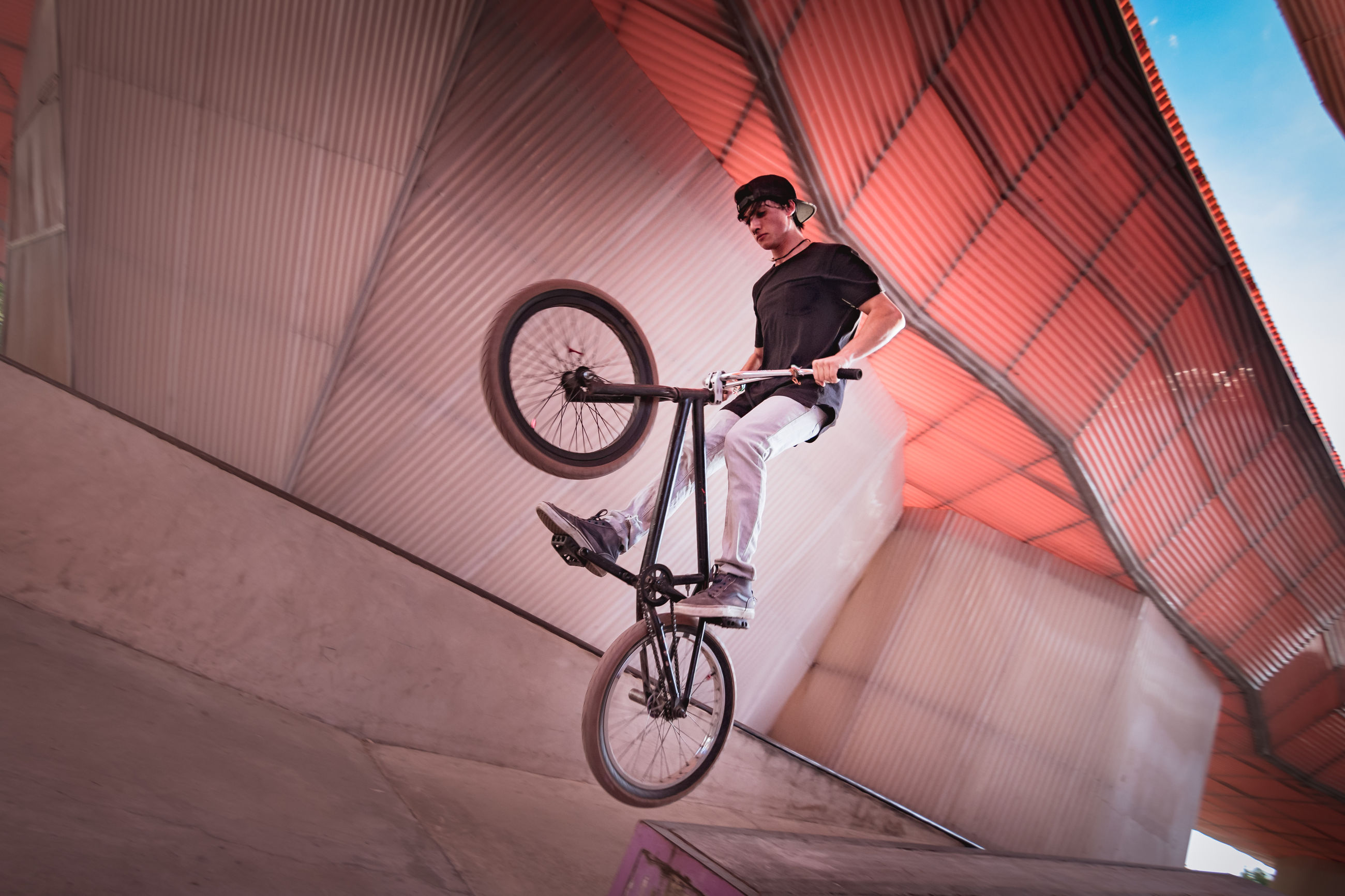 Young man riding bicycle on ramp at park