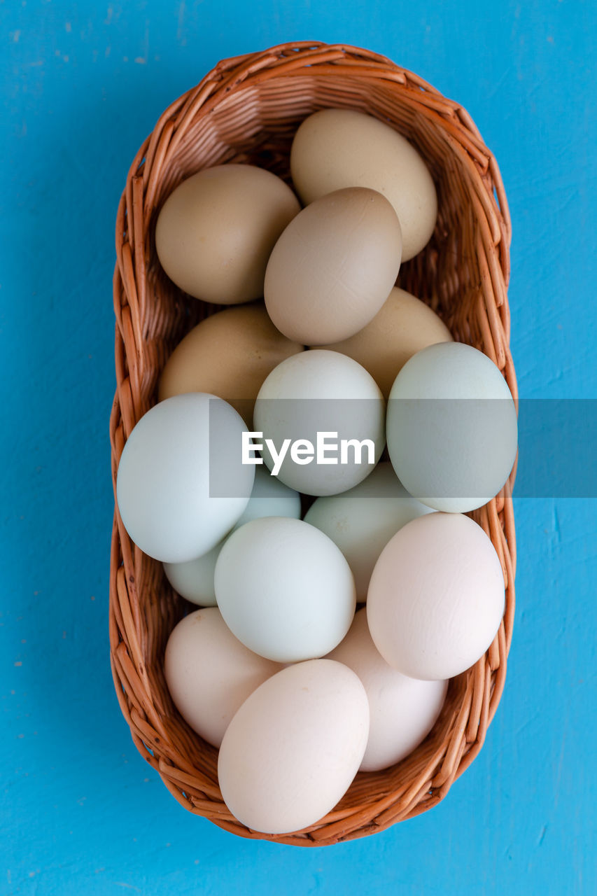 food and drink, food, egg, indoors, container, no people, freshness, wellbeing, blue, still life, healthy eating, high angle view, basket, directly above, close-up, studio shot, table, raw food, brown, group of objects, blue background, turquoise colored