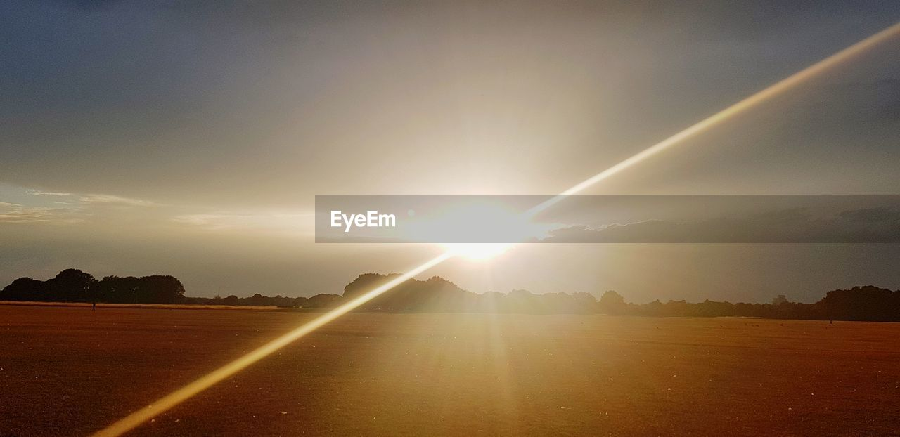 sky, lens flare, sunbeam, sun, sunlight, scenics - nature, beauty in nature, sunset, tranquil scene, nature, cloud - sky, environment, tranquility, no people, landscape, field, land, tree, non-urban scene, outdoors, bright, streaming, solar flare