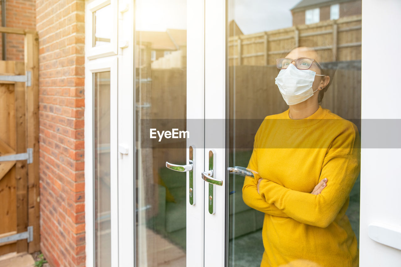 Woman wearing mask standing by window at home