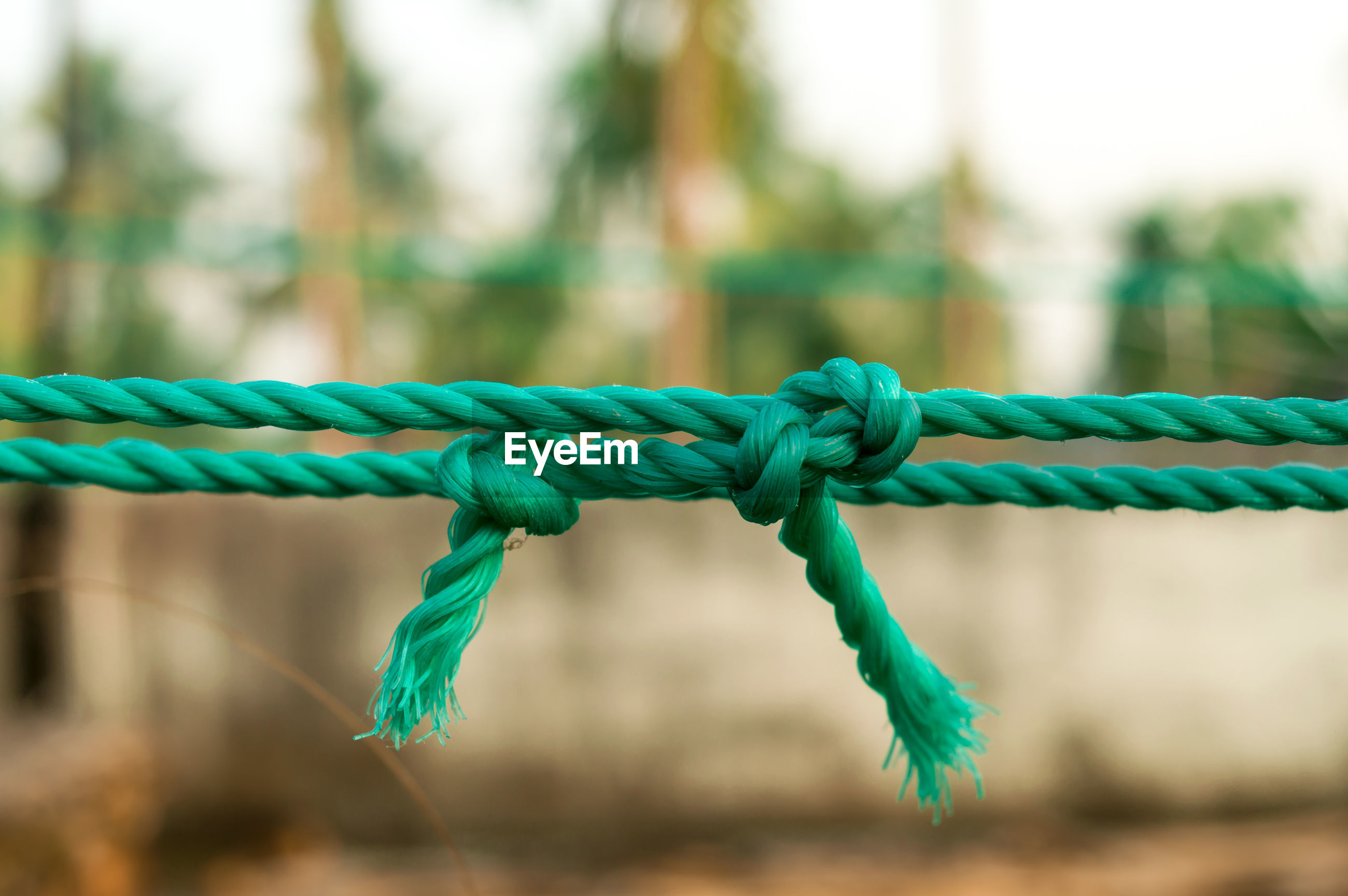 CLOSE-UP OF ROPE TIED ON FENCE