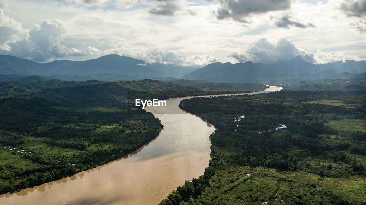AERIAL VIEW OF RIVER AMIDST MOUNTAINS AGAINST SKY