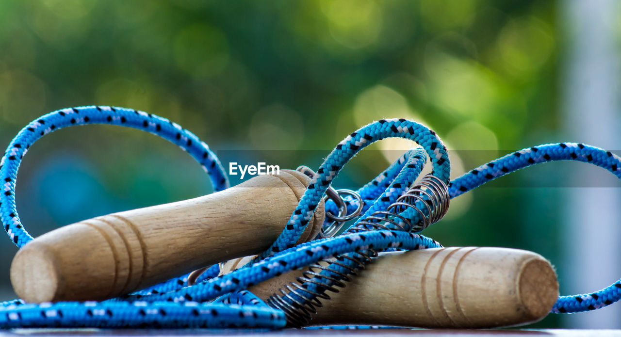 blue, close-up, focus on foreground, day, bracelet, no people, wood - material, rope, outdoors, art and craft, selective focus, table, creativity, craft, green color, equipment, pattern, still life, man made object, turquoise colored