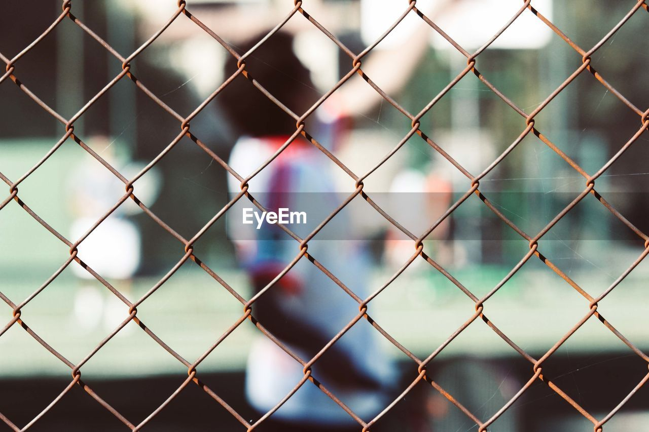 FULL FRAME SHOT OF CHAINLINK FENCE AGAINST BLURRED BACKGROUND SEEN THROUGH METAL WIRE