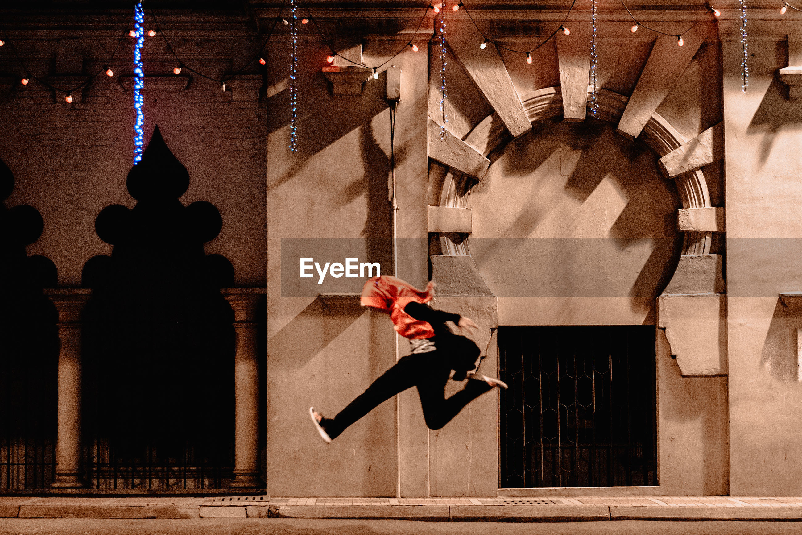 A girl in hijab jumping along the city street at night