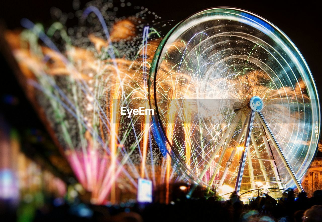 Illuminated Ferris Wheel And Fireworks At Night