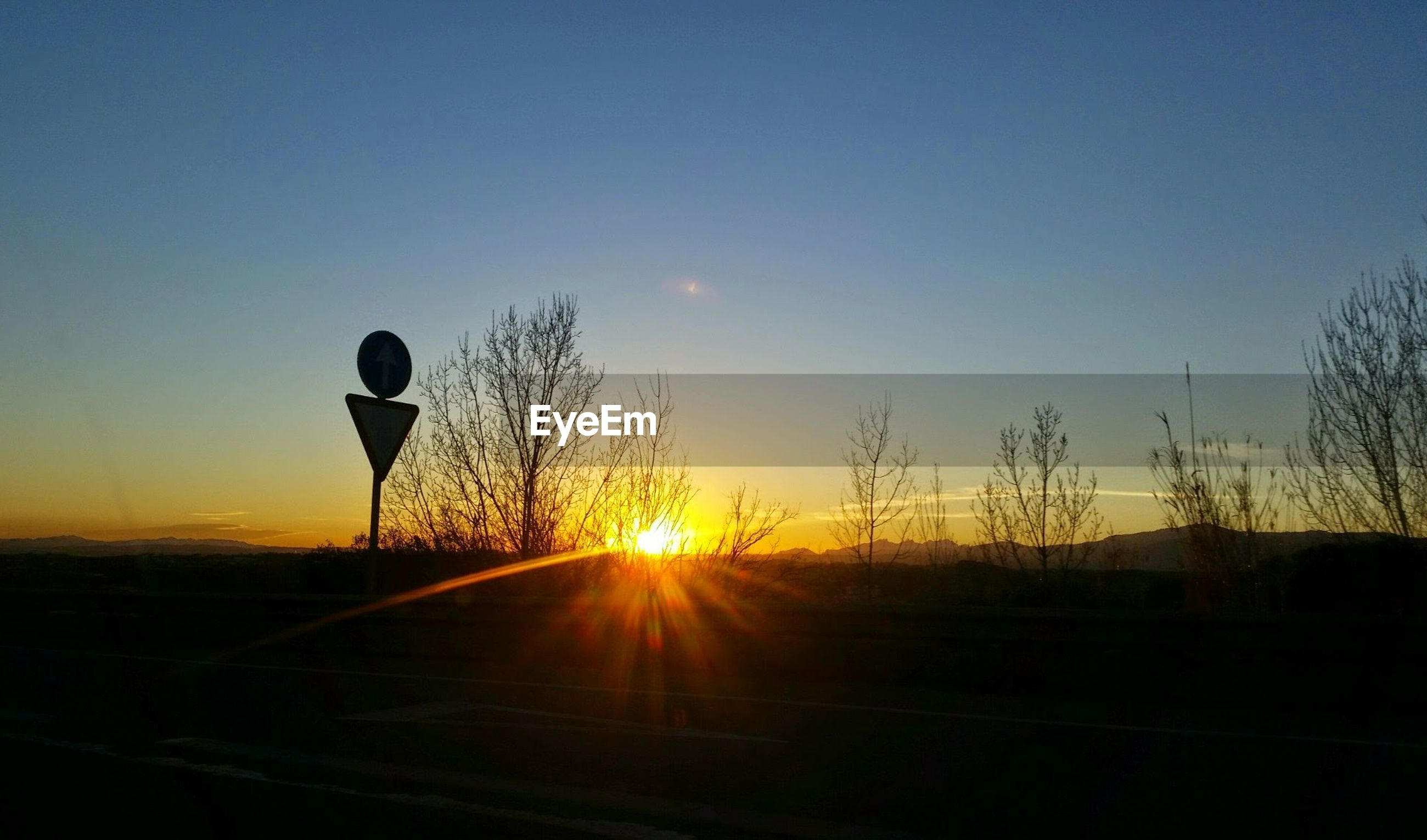 SILHOUETTE OF CAR ON ROAD AGAINST SKY DURING SUNSET