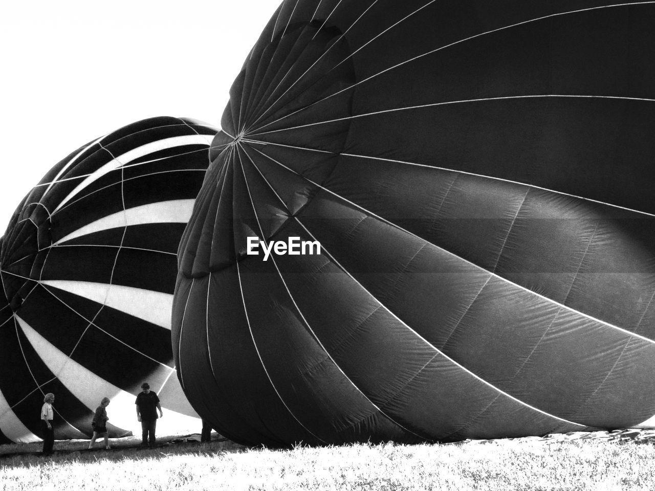 People Preparing Hot Air Balloons Against Clear Sky