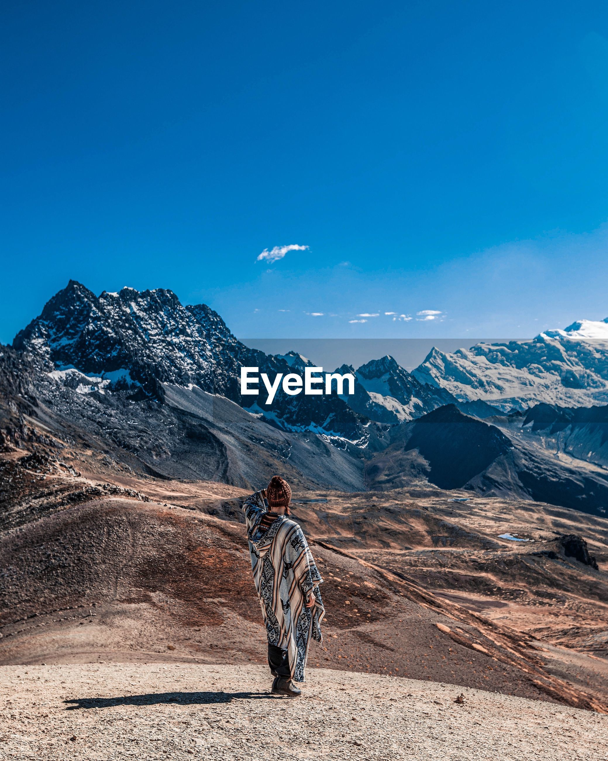 Rear view of woman standing on mountains against blue sky