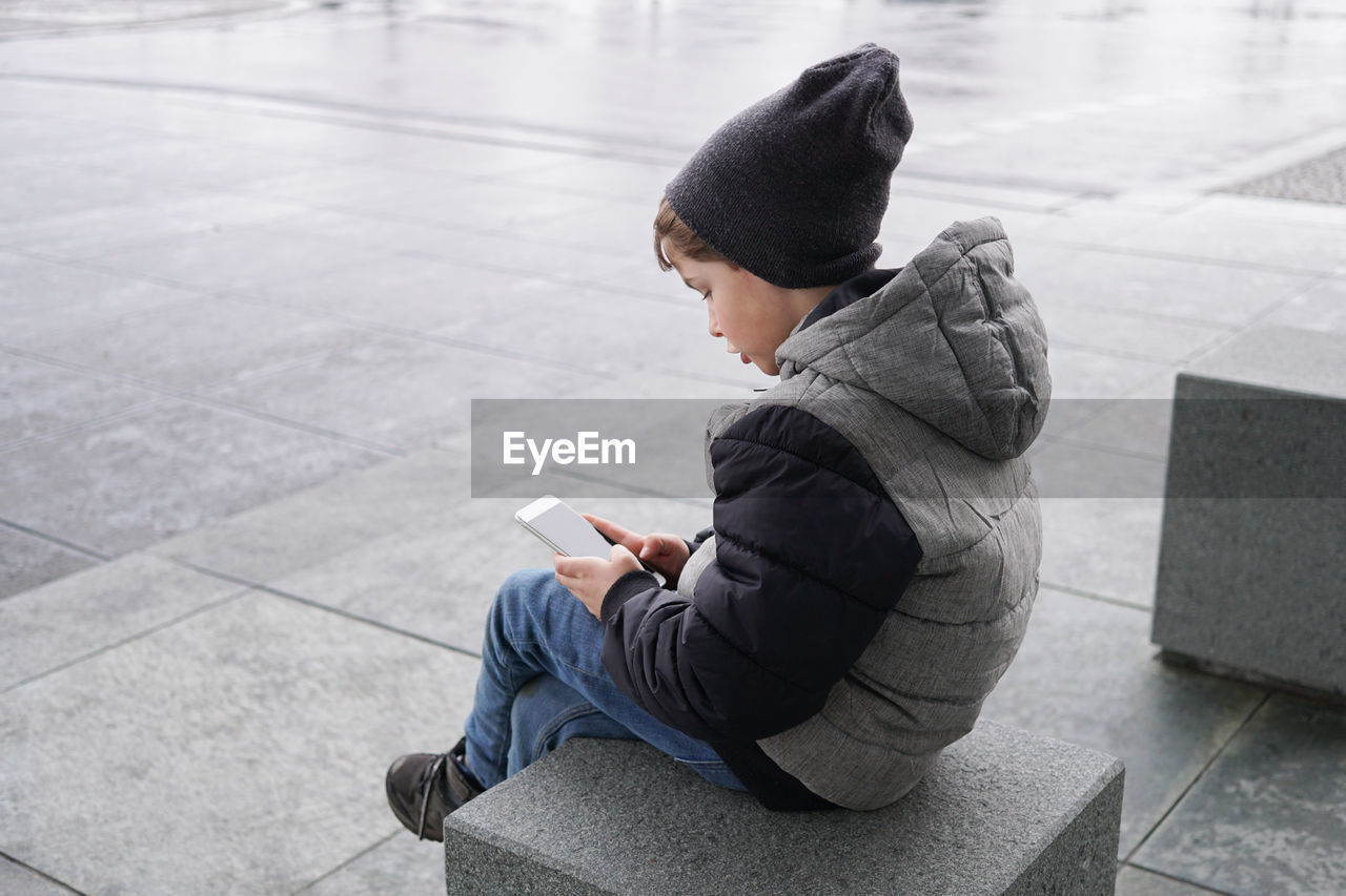 Boy Using Phone While Sitting On Seat During Winter