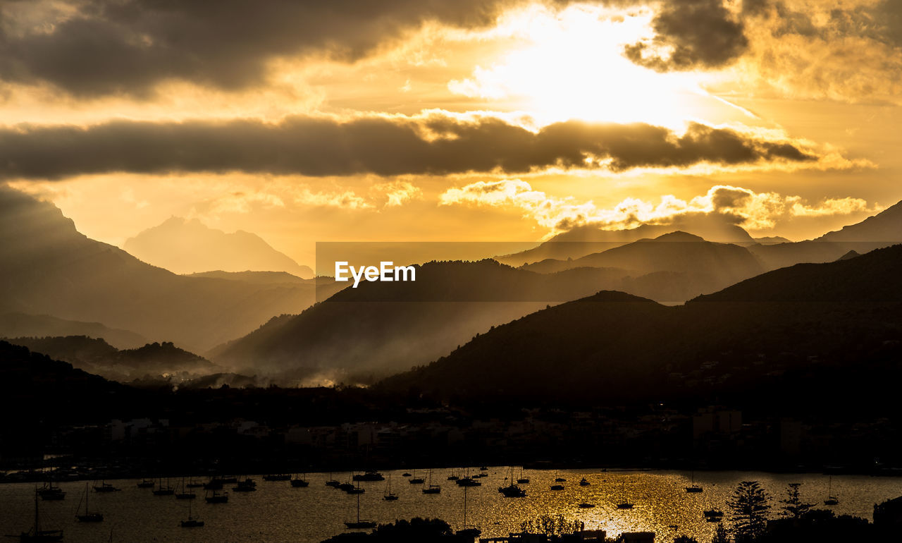 Scenic View Of Silhouette Boats In Harbor And Mountains Against Sunset Sky