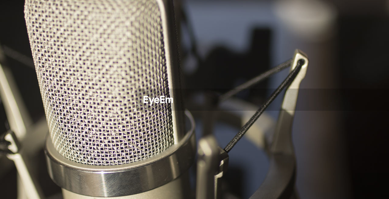 close-up, microphone, technology, input device, focus on foreground, arts culture and entertainment, music, no people, selective focus, indoors, metal, communication, equipment, sound recording equipment, pattern, silver colored, extreme close-up, audio equipment, still life
