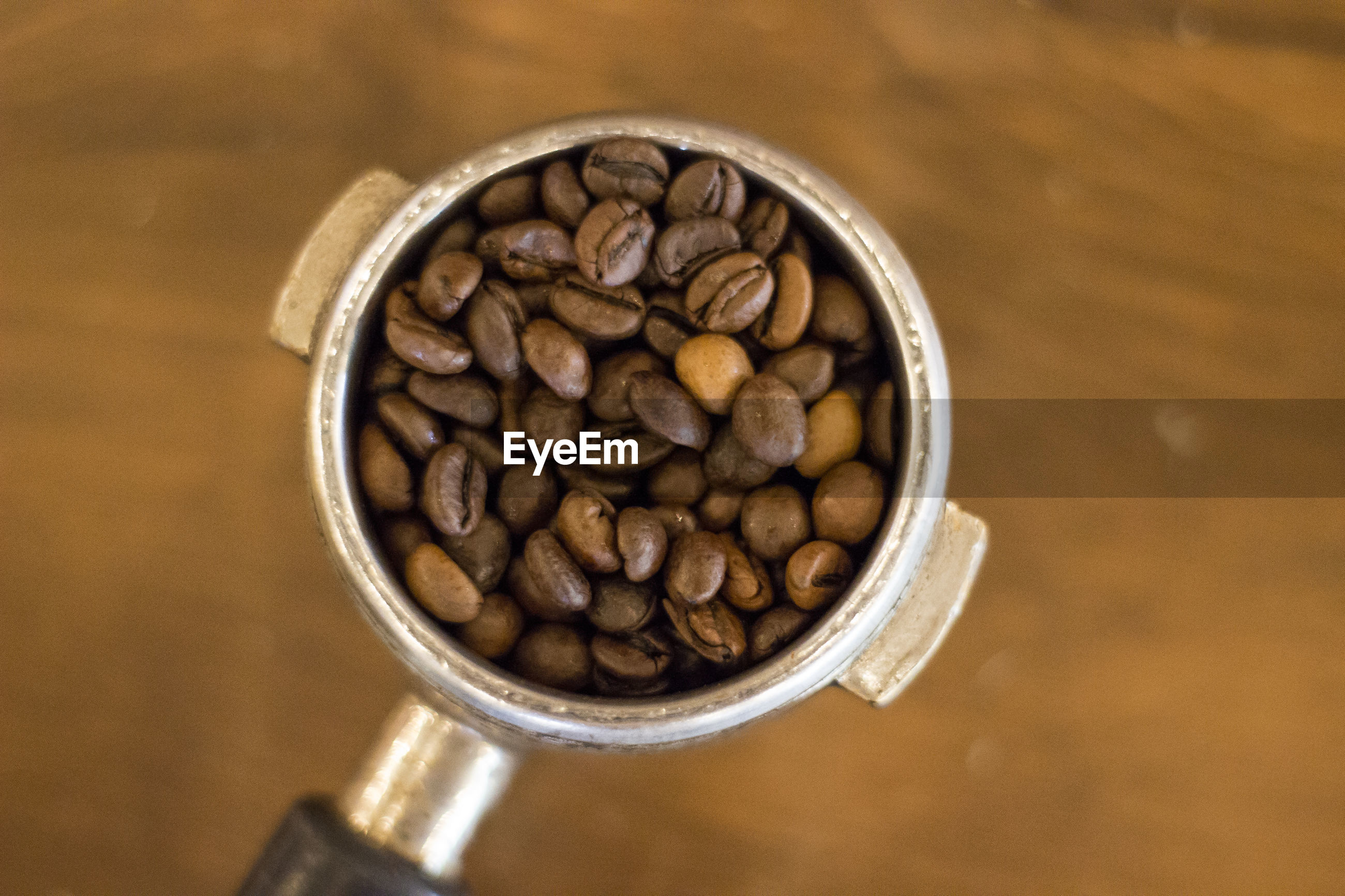 High angle view of coffee beans in container on table