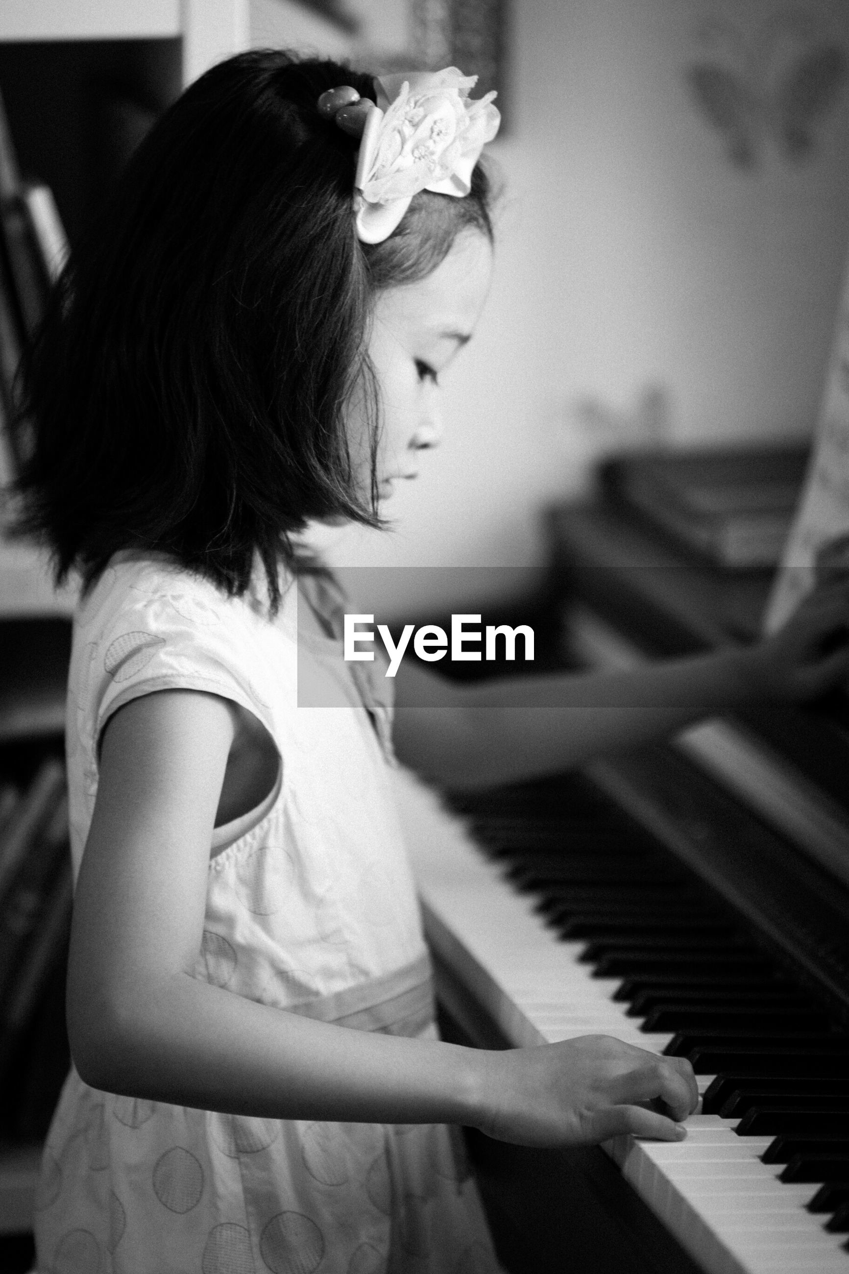 Side view of girl playing piano