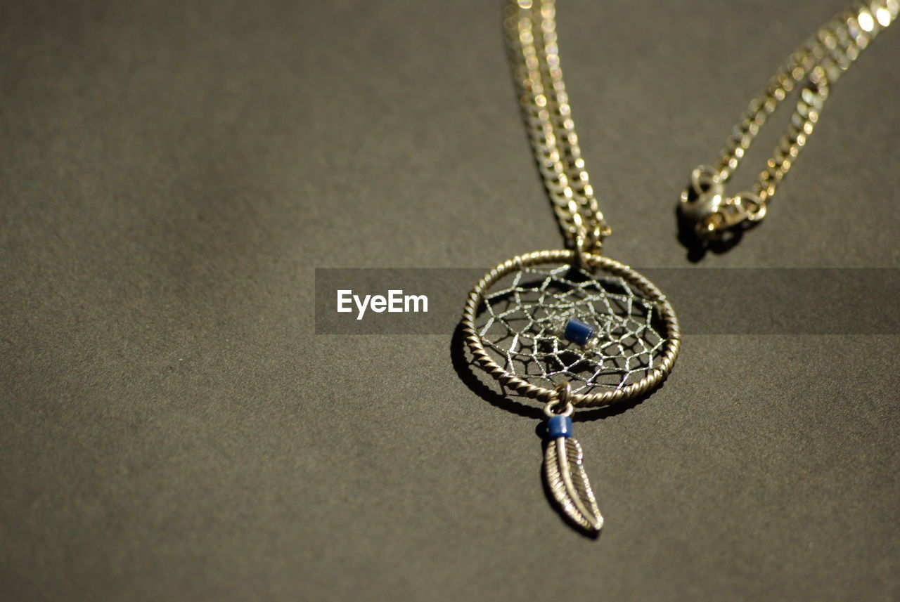 jewelry, necklace, no people, pendant, indoors, close-up, circle, diamond - gemstone, single object, chain, gold colored, metal, art and craft, shape, religion, locket, geometric shape, high angle view, shiny, religious equipment, personal accessory, silver colored, luxury