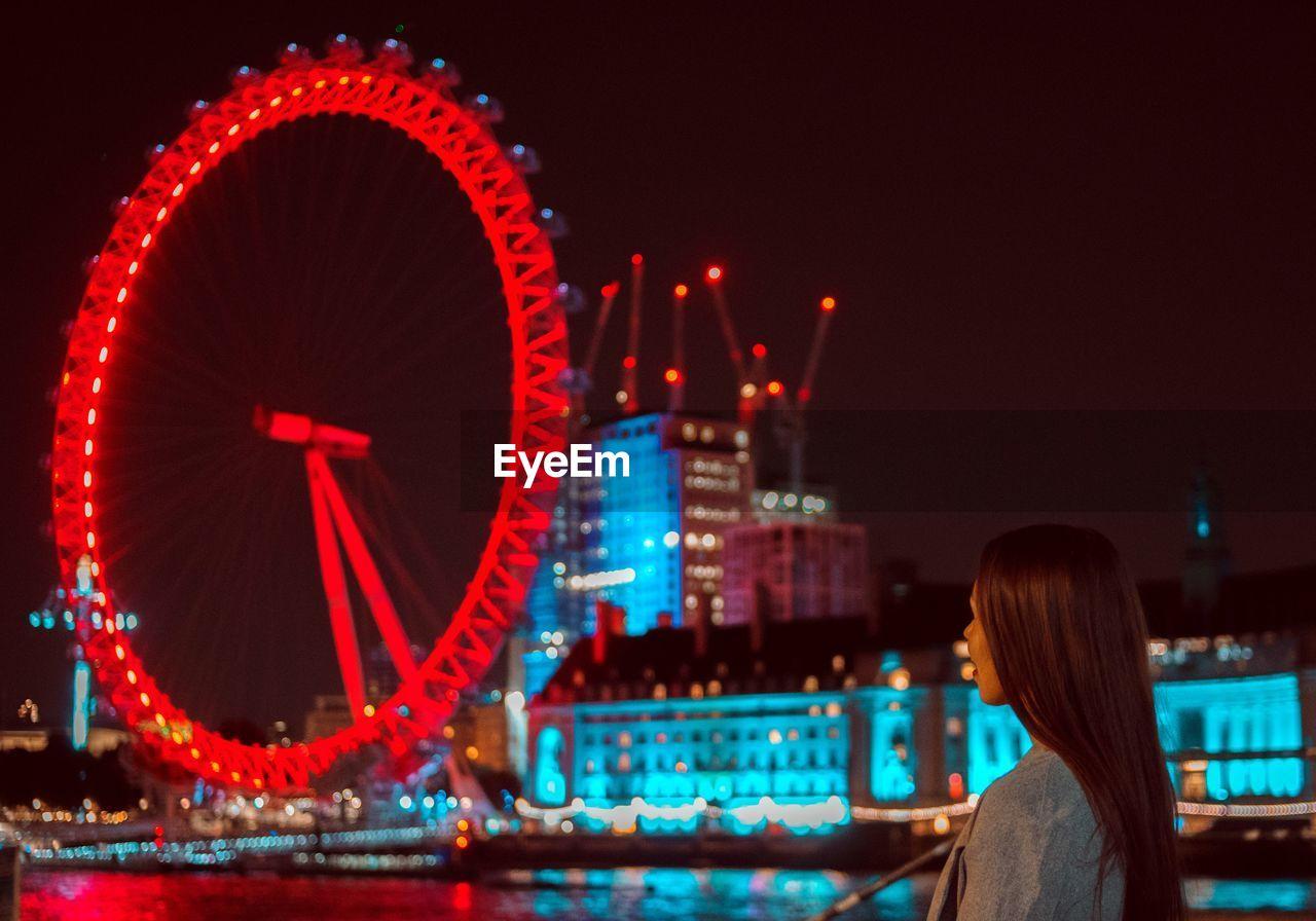 Woman Looking At Illuminated Ferris Wheel Against Sky At Night