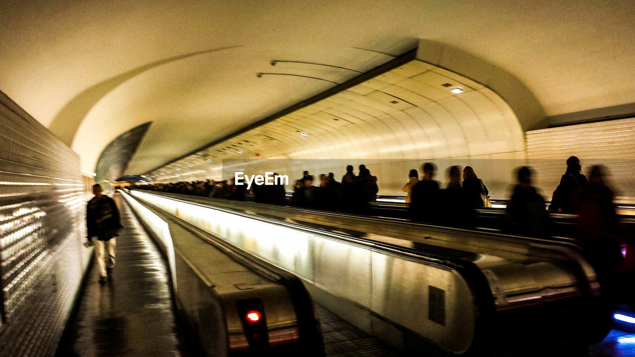 Blurred Image Of People At Moving Walkway In Illuminated Building