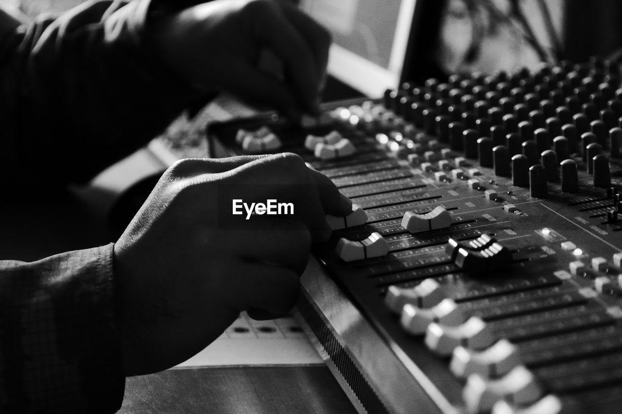 Cropped Hands Of Man Adjusting Sound Mixer Knobs