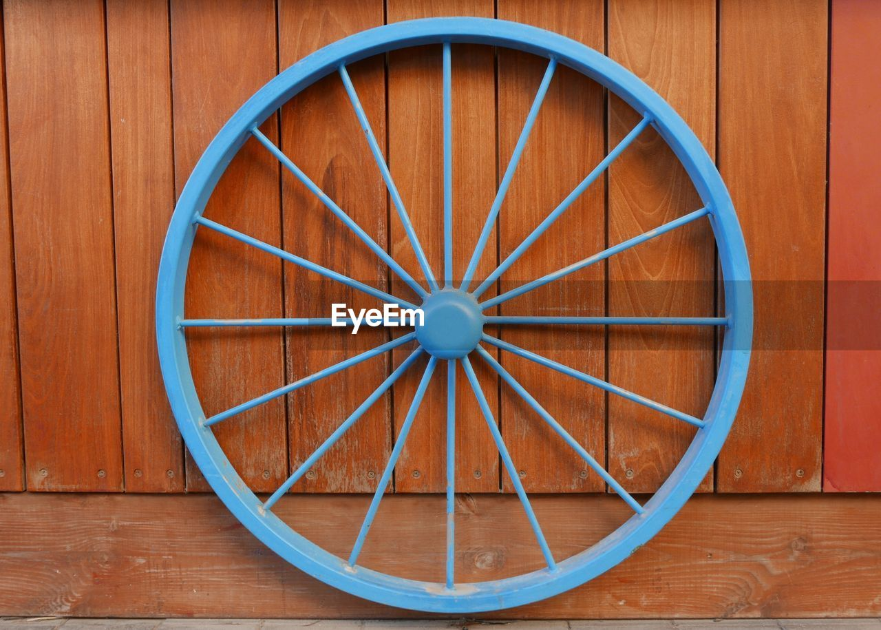 Blue Wheel Mounted On Wooden Wall