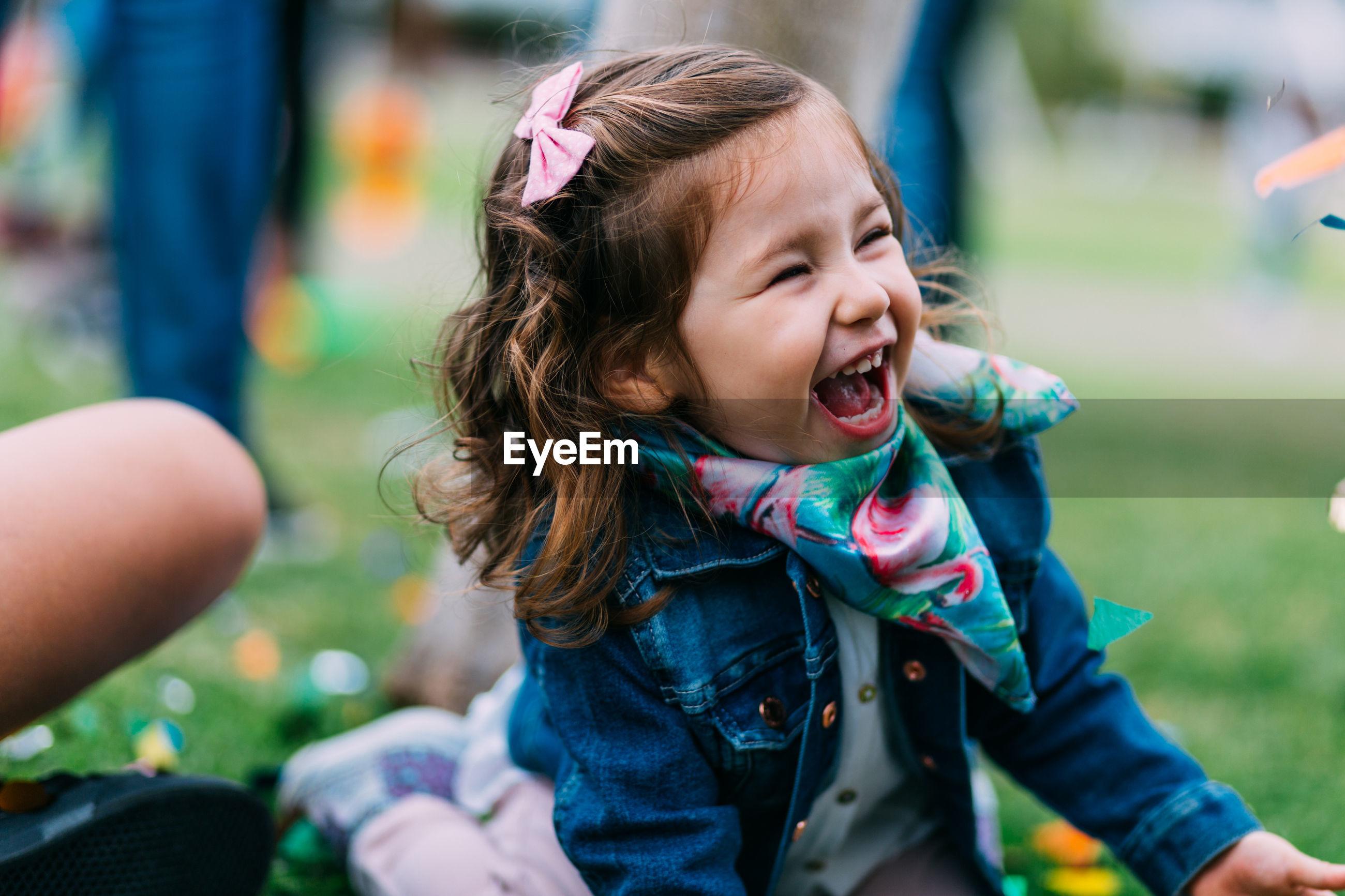 Cute cheerful girl sitting in park