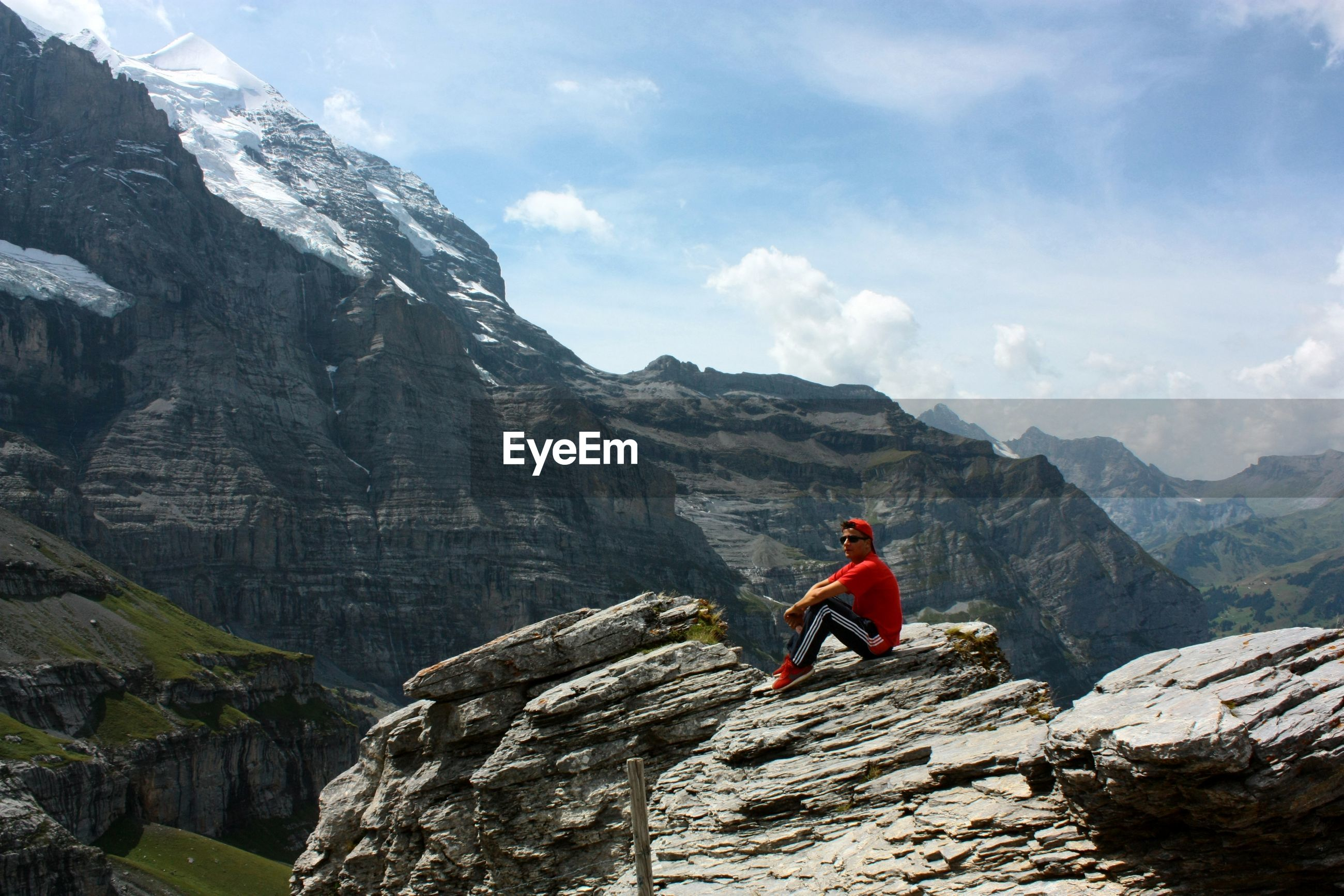 MAN ON ROCKS AGAINST MOUNTAINS