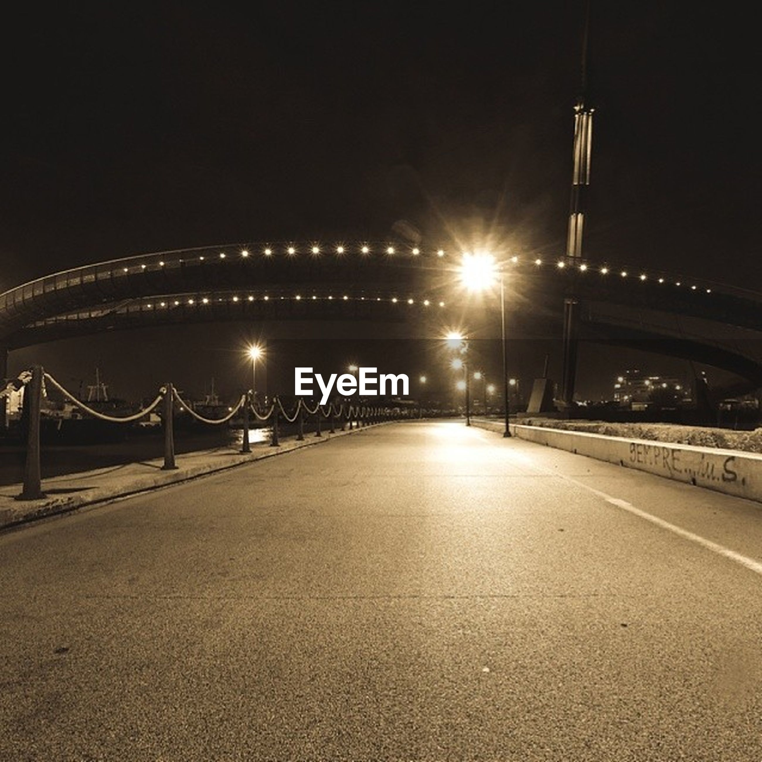 illuminated, night, the way forward, street light, transportation, diminishing perspective, built structure, lighting equipment, architecture, vanishing point, connection, empty, road, bridge - man made structure, clear sky, long, sky, street, copy space, outdoors