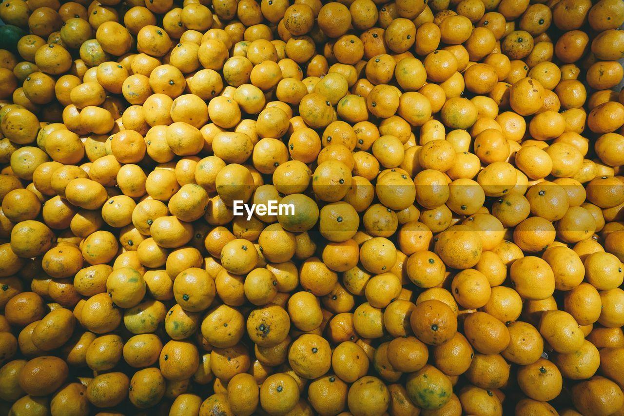 Full Frame Shot Of Orange Fruits At Market For Sale