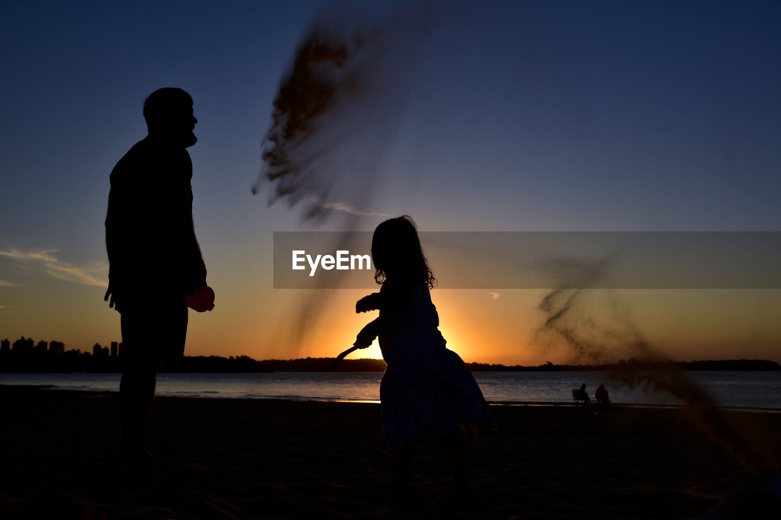Silhouette father and daughter throwing sand at beach against sky during sunset
