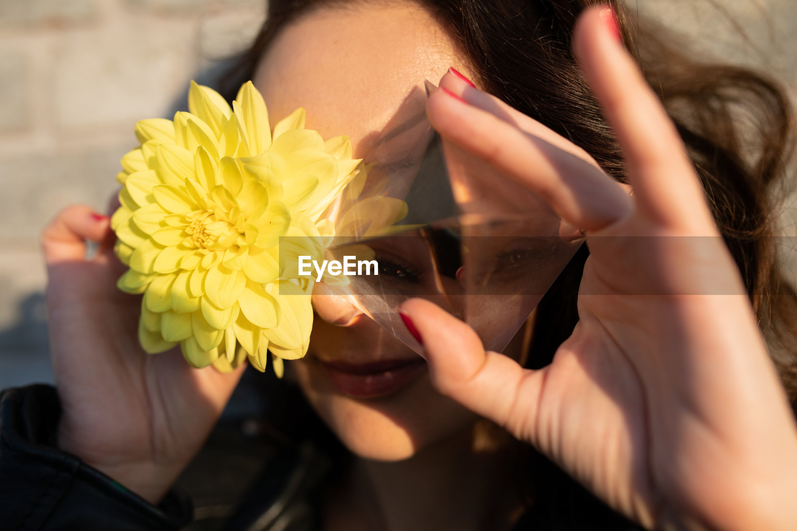 Close-up of woman holding yellow flower and crystal