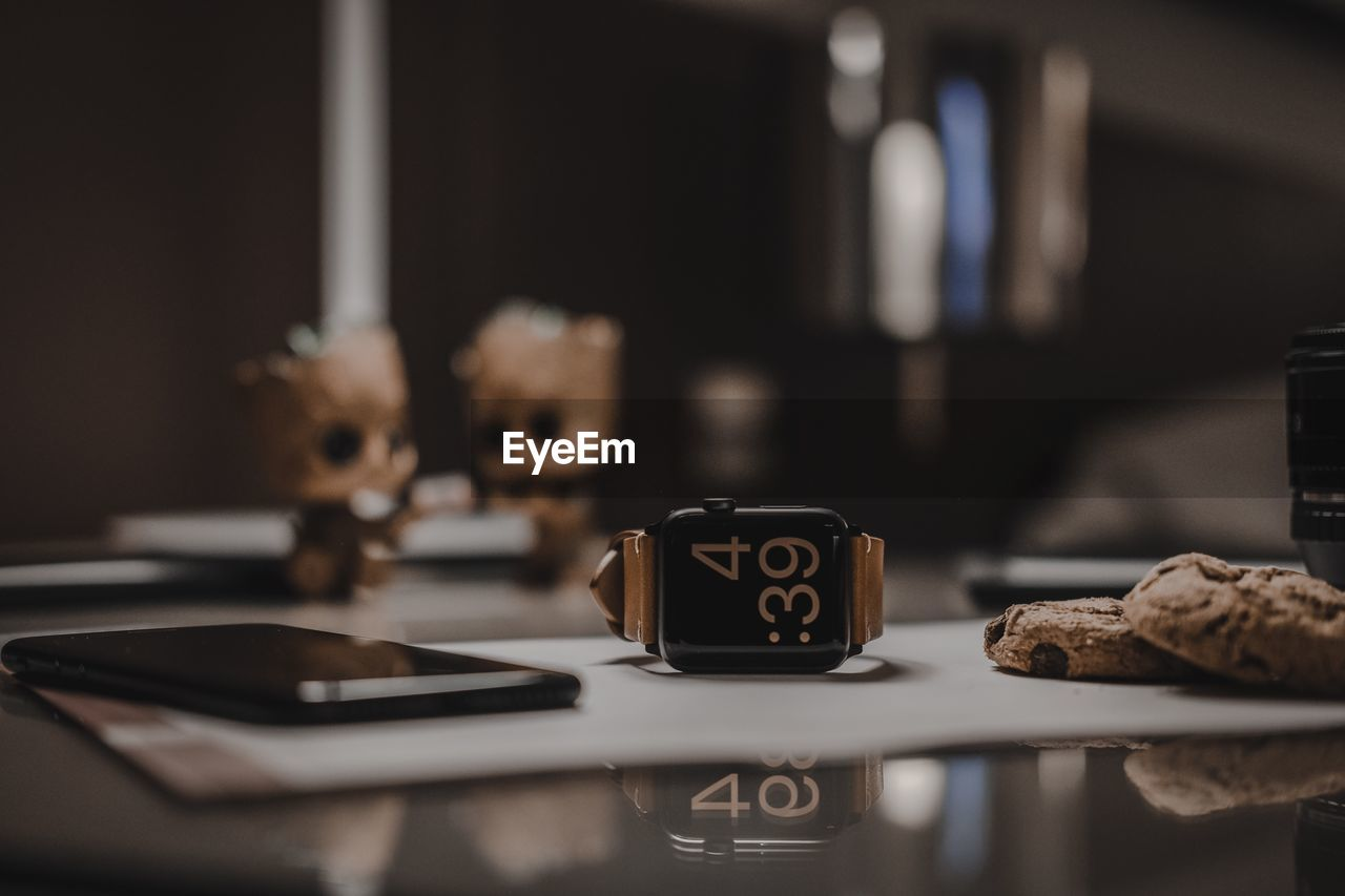 Close-Up Of Mobile Phone And Wristwatch With Cookies On Table